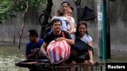지난 20일 태풍 '풍웡'으로 피해를 입은 필리핀 마닐라 인근 리잘 지역에서 주민들이 개조한 자전거를 타고 침수된 도로를 건너고 있다.