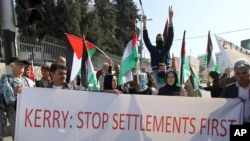 "Palestinski demonstranti nose transparent na kojem piše: ""Keri obustavi prvo izgradnju naselja"""
