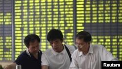 Investor berdiskusi di sebuah kantor broker saham di Nantong, provinsi Jiangsu, China (3/7).
