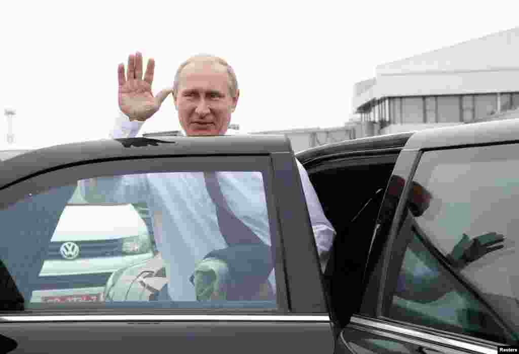 Russian President Vladimir Putin waves as he gets into a car upon his arrival at an airport outside Minsk, Aug. 26, 2014.
