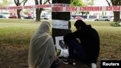 뉴질랜드 크라이스트처치 알 누르 이슬람 사원 앞에 임시로 마련된 추모 공간에서 시민이 숨진 희생자들을 애도하고 있다.