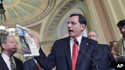 Sen. John Barrasso [C] quotes a USA Today article about gas prices as he and Sen. Lamar Alexander [L] and Senate Republican leader Mitch McConnell [R] speak to reporters, at the Capitol in Washington, D.C., May 17, 2011