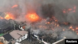 A fire engulfs houses and stores, near JR Itoigawa Station, in Itoigawa, Niigata Prefecture, Japan, in this photo taken by Kyodo, Dec. 22, 2016.