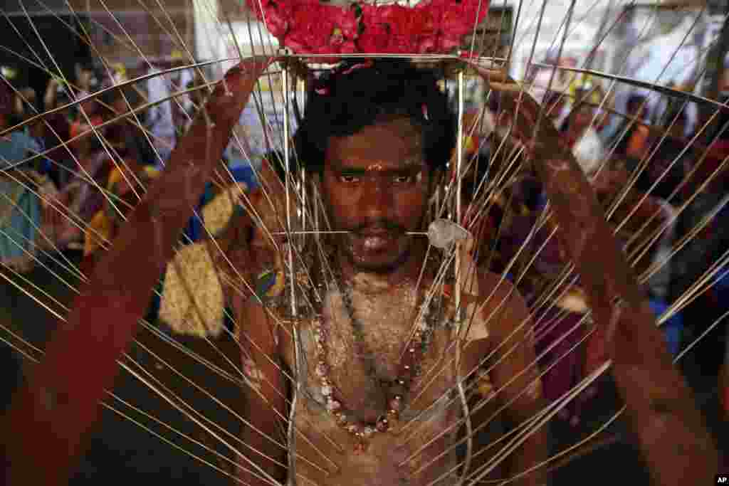 A Hindu devotee, body pierced with skewers, participates in a religious procession during Panguni Uthiram festival in Chennai, India.