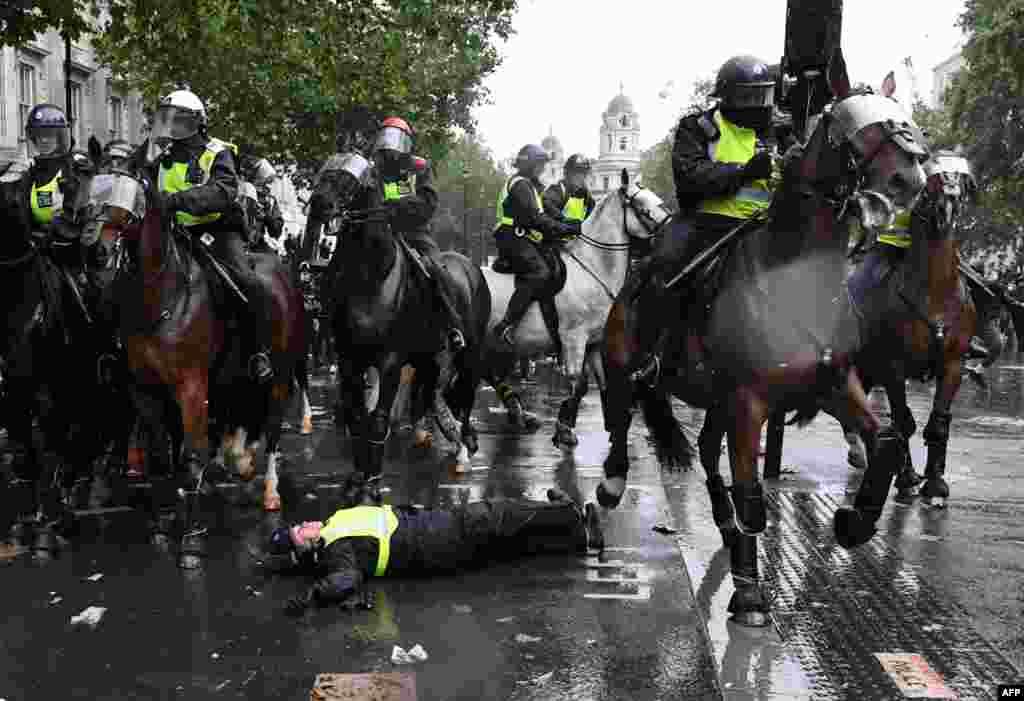 ប៉ូលិសជិះសេះចុះពីសេះរបស់ខ្លួន និងដេកនៅលើដី នៅក្នុងបាតុកម្មមួយនៅលើផ្លូវ Whitehall នៅក្នុងក្រុងឡុងដ៍ កាលពីថ្ងៃទី៦ ខែមិថុនា ឆ្នាំ២០២០ ដើម្បីបង្ហាញពីភាពរួបរួមជាមួយនឹងចលនា Black Lives Matter ដែលកើតឡើងដោយសា