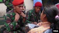 Seorang tenga medis Kopassus sedang memeriksa Ibu dan seorang anaknya yang sedang sakit di salah satu tempat penampungan korban Merapi.