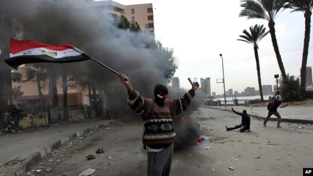 A protester part of the Black Bloc, holds the Egyptian national flag during clashes with riot police near Tahrir Square, Cairo, Egypt, Jan. 28, 2013.