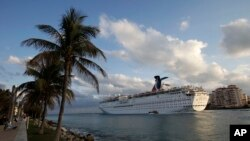 FILE - The Carnival Imagination cruise ship passes South Pointe Park in Miami Beach, Fla. as it leaves the Port of Miami.