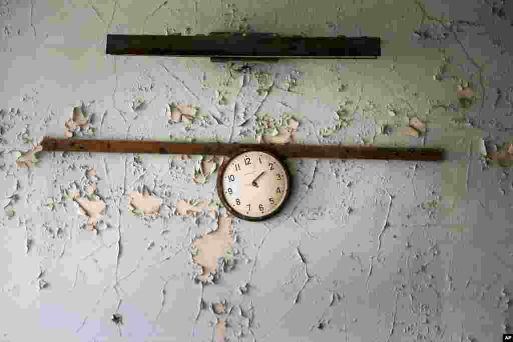 A broken clock hangs on a wall in a school in the deserted town of Pripyat, some 3 kilometers from the Chernobyl nuclear power plant Ukraine.