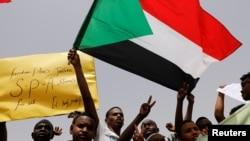 Les manifestants agitent des drapeaux soudanais, tiennent des banderoles et scandent des slogans lors d'une manifestation devant le ministère de la Défense à Khartoum, au Soudan, le 18 avril 2019.