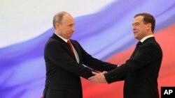នៅខាងឆ្វេង លោក វ្ល៉ាដឹមៀរ ពូទីន ចាប់ដៃជាមួយនឹងអតីតប្រធានាធិបតី Dmitry Medvedev ក្នុងពិធីសម្ពោធមួយក្នុងវិមានក្រឹមឡាំង នៃរដ្ឋធានីម៉ូស្គូ កាលពីថ្ងៃទី៧ ឧសភា ២០១២។ (AP Photo/RIA Novosti Kremlin, Yekaterina Shtukina, Presidential Press Service)