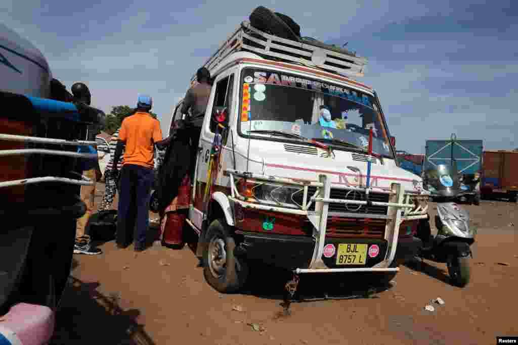 Des passagers montent dans un bus à Serrekunda, dans la capitale gambienne, Banjul, le 17 janvier 2017.