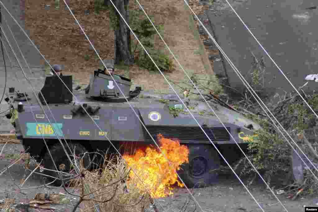 Tentara Nasional Venezuela mengamati api di bawah tank mereka, yang dipicu oleh bom Molotov dalam sebuah protes melawan pemerintahan Presiden Nicolas Maduro di San Cristobal, sekitar 660 km barat daya ibukota Caracas (27/2).