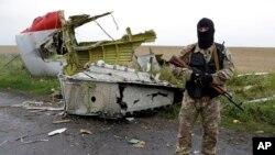 یک جدائی خواه طرفدار روسیه از محل سقوط هواپیما مرافبت می کند