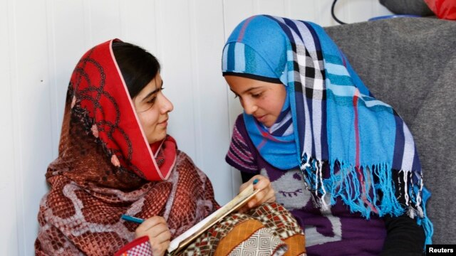 Pakistani teenage activist Malala Yousafzai (L), who was shot in the head by the Taliban for campaigning for girls' education, talks to Syrian refugee Mazoon Rakan, 16, about Mazoon's experience in the camp during her visit to the Zaatri refugee camp, in