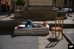 A homeless man sleeps on top of two mattresses in a street in downtown Madrid, Spain, Friday, Aug. 6, 2021. According to reports, poverty has increased considerably in the last months as Spain has been in lockdown to fight the coronavirus pandemic. (AP Photo)