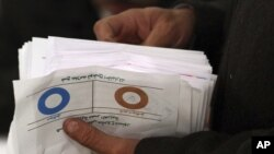 Seorang petugas pemilu menghitung perolehan suara yang menyatakan 'Tidak Setuju' di salah satu TPS di Bani Sweif, 115 kilometer sebelah selatan Kairo (22/12). Komisi pemilu Mesir mengumumkan hasil pemungutan suara di Mesir yang menyatakan 64 persen pemilih mendukung konstitusi baru dalam referendum tahap kedua bulan ini dan 36 persen lainnya menolak, Selasa (25/12).