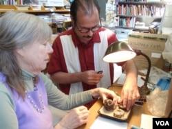 Donor Steven Martin and University of Idaho curator Priscilla Wegars examine and catalogue the donated opium artifacts.(VOA/T. Banse)