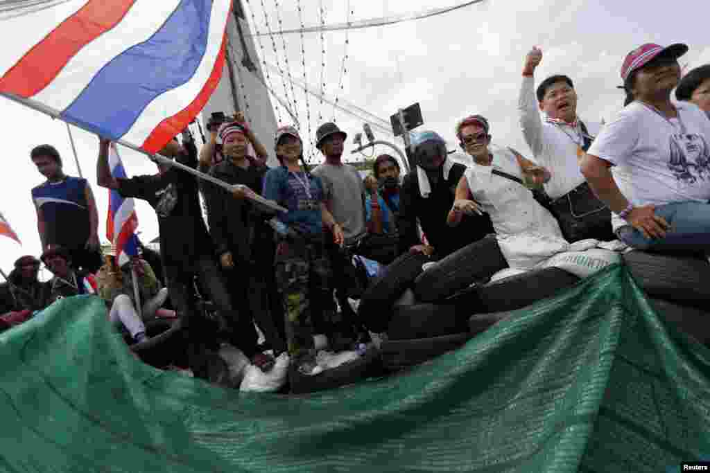 Anti-government protesters gesture from a barricade where they confront riot policemen near the Government House in central Bangkok, Feb. 14, 2014.