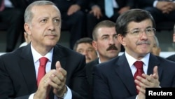 Turkish president-elect Tayyip Erdogan (L) and incoming prime minister Ahmet Davutoglu applaud during the Extraordinary Congress of the ruling AK Party (AKP) in Ankara, Aug. 27, 2014.
