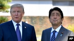 U.S. President Donald Trump, left, meets with Prime Minister Shinzo Abe upon the arrival at the Kasumigaseki Country Club in Kawagoe, near Tokyo, Nov. 5, 2017.