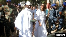 Gambian President Yahya Jammeh arrives at a polling station with his wife, Zineb, during the presidential election in Banjul, Gambia, Dec. 1, 2016.