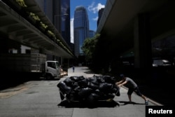 A worker pushes a cart loaded with garbage collected nearby to a refuse collection point at the financial Central District in Hong Kong, China, June 7, 2017.