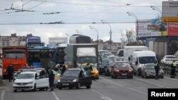Polisi lalu lintas memeriksa surat-surat pengendara dan penumpang mobil di sebuah pos pemeriksaan di Moskow, Rusia, 15 April 2020.