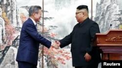 문재인 한국 대통령과 김정은 북한 국무위원장이 19일 평양공동선언문에 서명한 뒤 가진 공동 기자회견에서 악수하고 있다. 평양사진공동취재단.