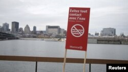 """A sign stating """"Don't touch the water"""" is seen near the St. Lawrence river as the city of Montreal is seen in the background, Nov. 11, 2015. Montreal, Canada's second-largest city, began dumping untreated sewage into the St. Lawrence River on Wednesday."""