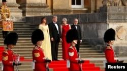 Premye Minis britanik la, Theresa May, avèk mari li, Philip (adwat), ki kanpe bò kote Pezidan Donald Trump ak Premyè Dam Lèzetazini an, Melania, nan antre Palè Blenheim nan, tou prè Inivèsite Oxford la, kote yo ta pral asiste yon dine nan konpayi kèk envite espesyal, pami yo te genyen divès òm dafè britanik. Gad britanik, an inifòm tradisyonèl, t ap asire sekirtie a. (Foto: REUTERS, 12 jiyè 2018).