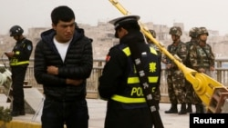 Seorang polisi memeriksa kartu identitas seorang pria etnis Muslim Uighur saat patroli di jalan-jalan kota Kashgar, Xinjiang, China (foto: ilustrasi).