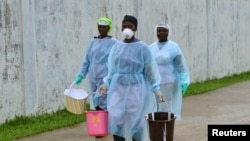 Health workers carry buckets of disinfectant at the newly-constructed Island Clinic and Ebola treatment center in Monrovia, Liberia, Sept. 25, 2014.