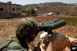 FILE - A Hezbollah fighter uses binoculars to scan for Israeli forces' positions, on the outskirts of the village of Aitaroun, near the town of Bint Jbeil, Aug. 16, 2006. With Trump's rise to power, many members of the Shi'ite community in Lebanon are increasingly uneasy about the future.