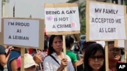 FILE - Indonesian gay activists hold posters during a protest demanding equality for lesbian, gay, bisexual and transgender people in Jakarta, May 21, 2011.