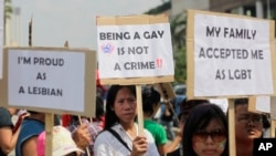 FILE - Indonesian gay activists hold posters during a protest demanding equality for LGBT (Lesbian, gay, bisexual and transgender) people in Jakarta, Indonesia, Saturday, May 21, 2011. Being gay or lesbian has never been outlawed in Indonesia, except in the province of Aceh.