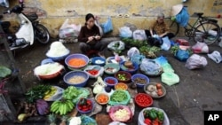 Vietnamese women gather to sell vegetables at a street market , in Hanoi. Vietnam's economy has braced market reform, but the recent boom may be facing some hard times (FILE).