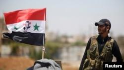 تصویر یک سرباز ارتش در کنار پرچم سوریه در حاشیه درعا - ۱۹ تیر ۱۳۹۷
