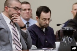 FILE - Larry Nassar sits with attorney Matt Newburg during his sentencing hearing in Lansing, Michigan, Jan. 24, 2018.