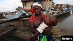 A woman sits in a canoe with her child as the metropolitan government begins the demolition of structures in the Makoko riverine community in Lagos, July 16, 2012. The structures were deemed illegal because they were built without permission on Lagos Lagoon.