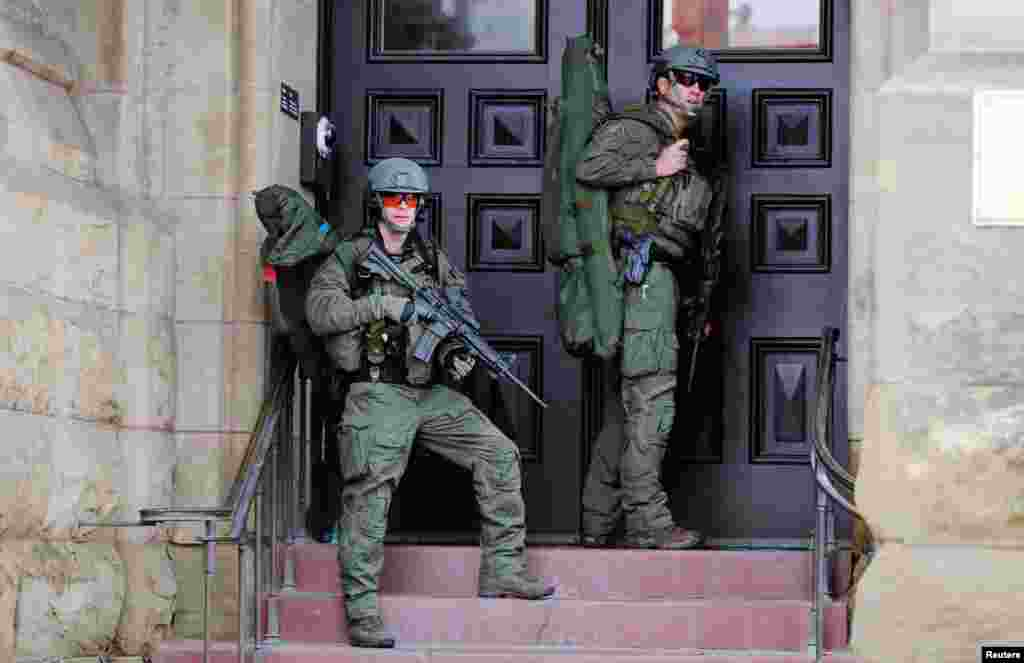 Armed RCMP officers guard the front of Langevin Block on Parliament Hilll following a shooting incident in Ottawa, Canada, Oct. 22, 2014.