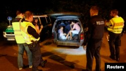 A group of migrants from Syria sits inside a vehicle stopped by German police on a country road heading to Freilassing, Germany, from Salzburg, Austria, Sept. 13, 2015.