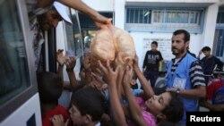 2014年7月19日巴勒斯坦儿童在拉法接受联合国面包