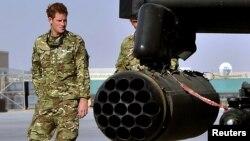 El príncipe Harry de Inglaterra camina junto a un helicóptero Apache.