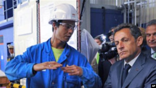 France's President Nicolas Sarkozy, right, listen to a worker during a visit at the Saint Nazaire naval plant, in Saint Nazaire, western France (File)