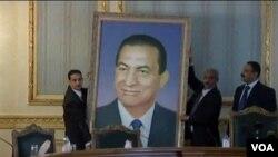 Ofisyèl nana Ejypt k ap desann pòtrè ansyen Prezidan Hosni Mubarak nan kabinè yon building nan Cairo