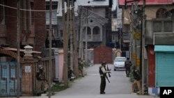 Tentara paramiliter India berlindung saat melakukan pencarian di sebuah perumahan penduduk saat terjadinya bentrokan di Srinagar, Srinagar, Indian Kashmir (13/3).