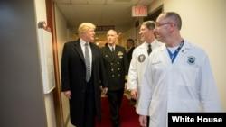 Tổng thống Donald Trump nói chuyện với (từ trái sang phải) Đại tá Mark Kobelja, giám đốc Trung tâm Y tế Quân đội Quốc gia Walter Reed; Bác sĩ Ronny Jackson, bác sĩ của tổng thống; và Bác sĩ James Jones, bác sĩ của tổng thống và giám đốc Đơn vị Thẩm định và Điều trị Y tế, ngày 12 tháng 1, 2018, ở Bethesda, bang Maryland.