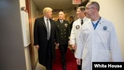 President Donald J. Trump talks with, from left to right, with Capt. Mark Kobelja, director of Walter Reed National Military Medical Center; Dr. Ronny Jackson, physician to the president; and Dr. James Jones, physician to the president and medical director of the Medical Evaluation and Treatment Unit, Jan. 12, 2018, in Bethesda, Md., following the president's annual physical at the medical facility.