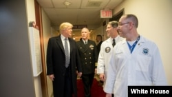 Perezida Donald J. Trump avugana na Capt. Mark Kobelja, ayoboye ibitaro Walter Reed National Military Medical Center; na Dr. Ronny Jackson, akurikirana amagara ya perezida muri White House.